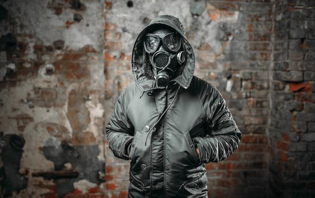 Soldado acosador en máscara de gas, hombre superviviente después de la guerra nuclear.