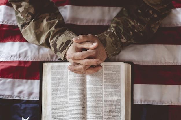 Soldado americano llorando y rezando con la bandera americana y la biblia delante de él.