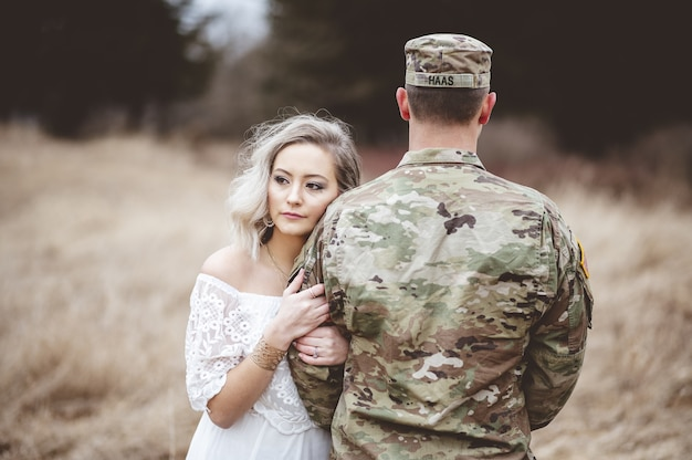 Soldado americano con su amada esposa de pie en un campo de hierba seca