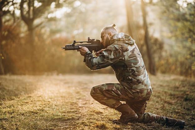 Soldado de camuflaje jugando airsoft al aire libre en el bosque