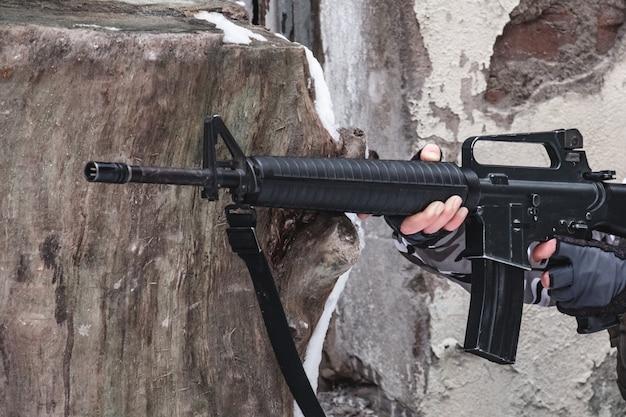 Un soldado contratado apunta con un rifle moderno cerca de una pared.