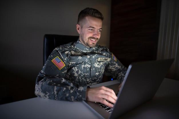 Soldado de ee.uu. en uniforme trabajando hasta tarde en la computadora enviando correo a su familia