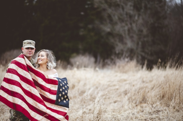 Soldado estadounidense con su esposa sonriente envuelta en una bandera estadounidense