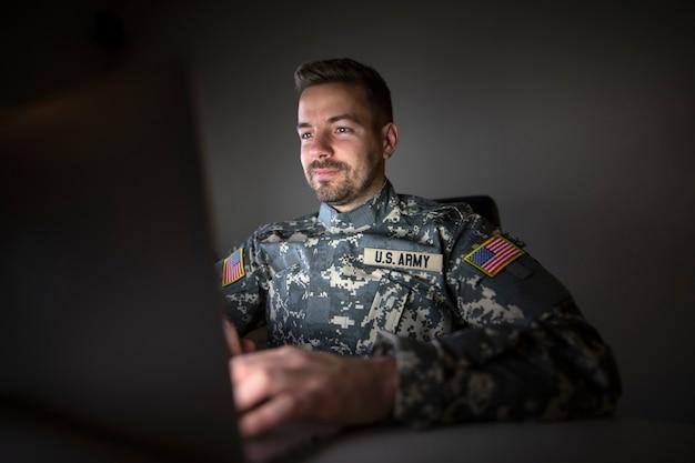 Soldado estadounidense en uniforme militar con banderas de parche de estados unidos trabajando hasta tarde en la computadora