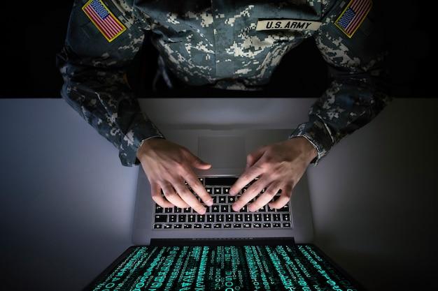 Soldado estadounidense en uniforme militar que previene un ataque cibernético en el centro de inteligencia militar
