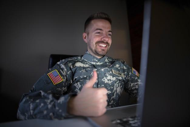 Soldado estadounidense en uniforme militar sosteniendo los pulgares hacia arriba frente a la computadora