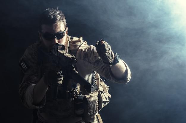 Soldado de las fuerzas especiales con rifle en la oscuridad