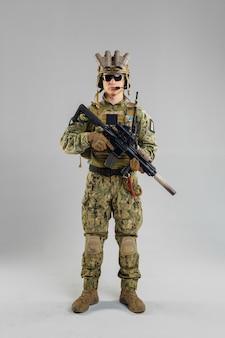 Soldado de las fuerzas especiales con rifle sobre fondo blanco.