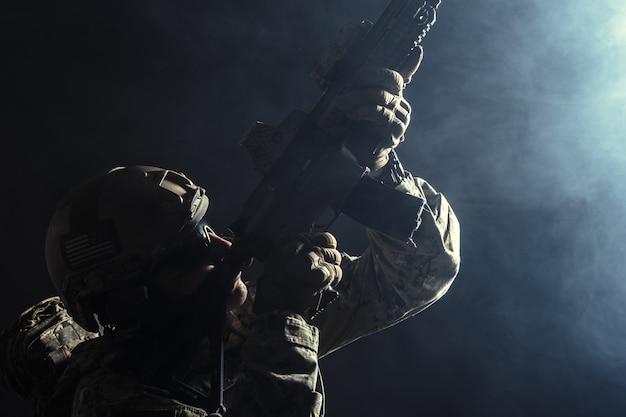 Soldado de las fuerzas especiales con rifle sobre fondo oscuro