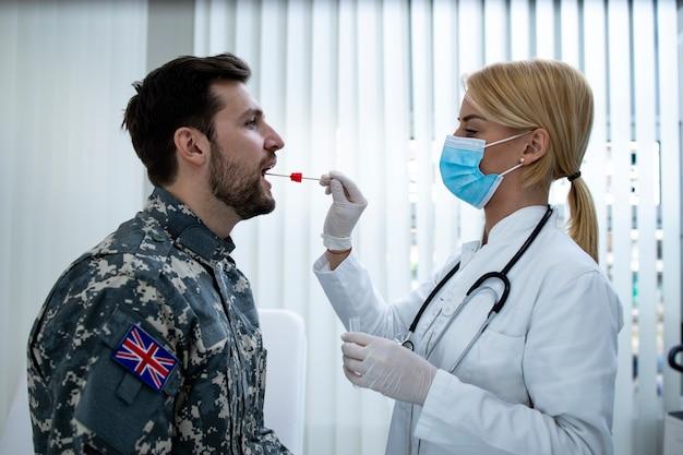 Soldado inglés en uniforme haciendo una prueba de pcr en el consultorio médico durante la epidemia del virus covid19