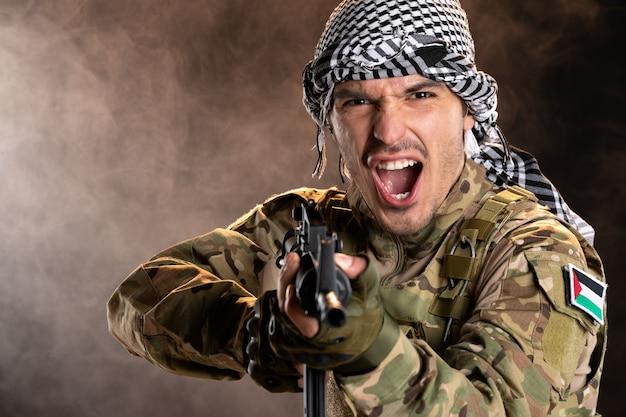 Soldado joven emocional en camuflaje en la pared oscura