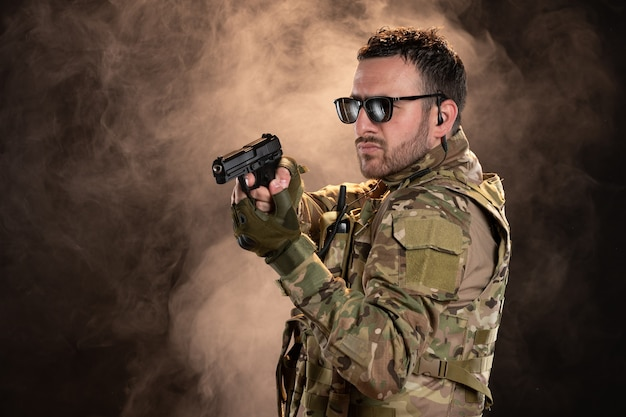 Soldado masculino en camuflaje con el objetivo de pistola en la pared oscura
