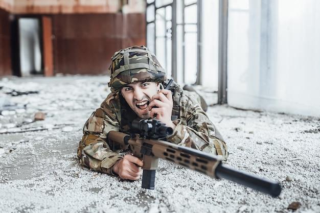 Soldado militar en el uniforme yacía en el suelo y lo sostiene en las manos de un gran rifle