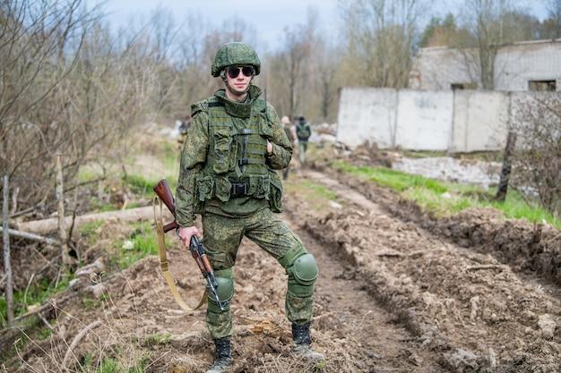 Soldado con rifle y binocular en uniforme de camuflaje y barril
