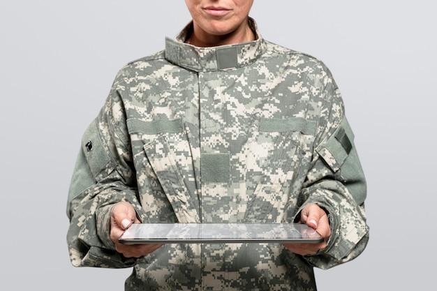Soldado de sexo femenino que sostiene una tecnología del ejército de la tableta
