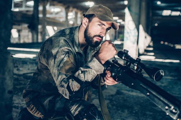 El soldado tranquilo y pacífico mira hacia adelante. el esta esperando. joven está sentado una rodilla. guy usa uniforme militar.
