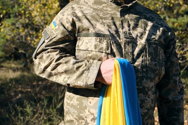 Soldado ucraniano sostiene en su mano la bandera amarilla-azul del estado, presionó su mano contra su pecho