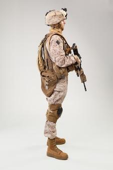 Soldado en uniforme de infantería de marina estadounidense con rifle en gris claro, foto de estudio
