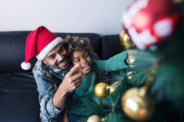 Soldado en uniforme sorprendiendo a su hija y celebrando la navidad juntos