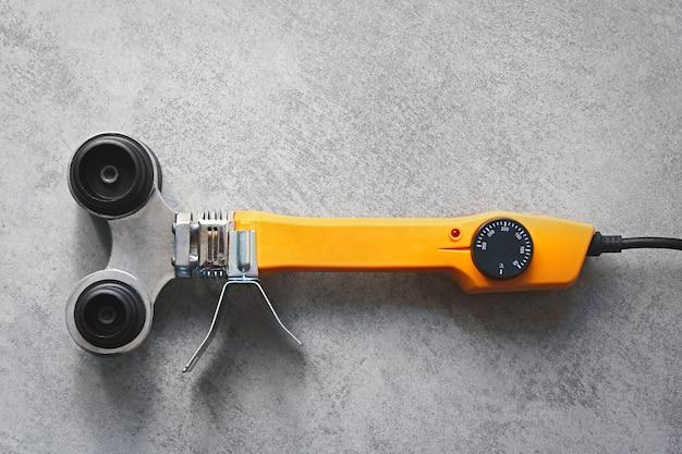 Soldador amarillo para tubos de pvc sobre fondo gris.