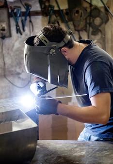 Soldador haciendo soldadura en un taller de metal