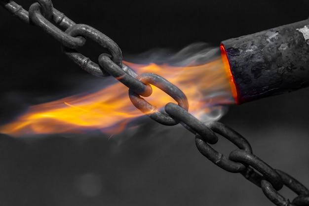 El soldador macho de primer plano suelda metal usando un quemador de gas. trabajador utilizar quemador de gas para piezas metálicas en un taller.