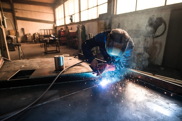 Soldador profesional soldando piezas de construcción de metal en taller industrial