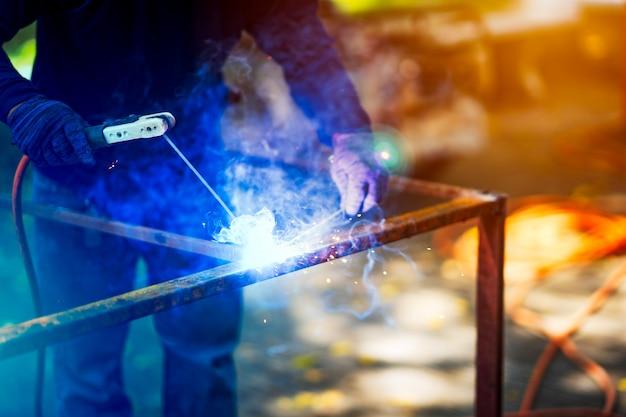 Soldador soldando estructura de hierro en sitio de construcción