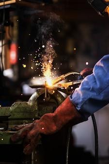 El soldador está soldando en el garaje, trabajador industrial en la estructura de acero de soldadura de fábrica