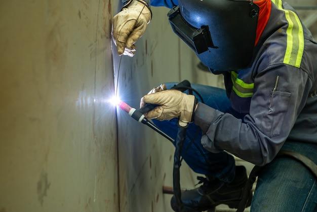 El soldador está soldando soldadura de gas inerte de tungsteno, antorcha de soldadura tig