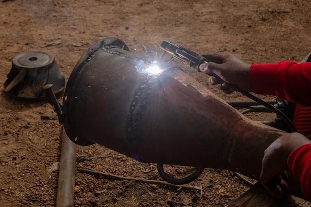 El soldador está soldando las tuberías de metal en el sitio de construcción