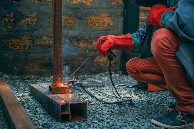 Soldador suelda una tubería de metal con soldadura eléctrica, sostiene un electrodo en sus manos