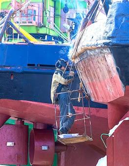 Un soldador trabajando en un barco de reparación.