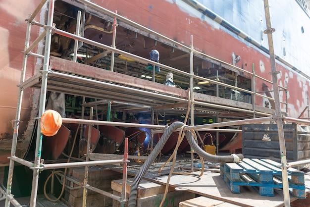 Soldador trabajando en el patio de reparación de buques - trabajo en caliente