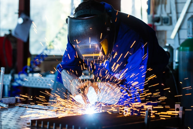 Soldadora soldadora de metal en taller con chispas.