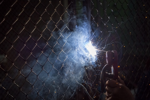 Los soldadores están soldando puertas para proteger la propiedad en el fondo oscuro