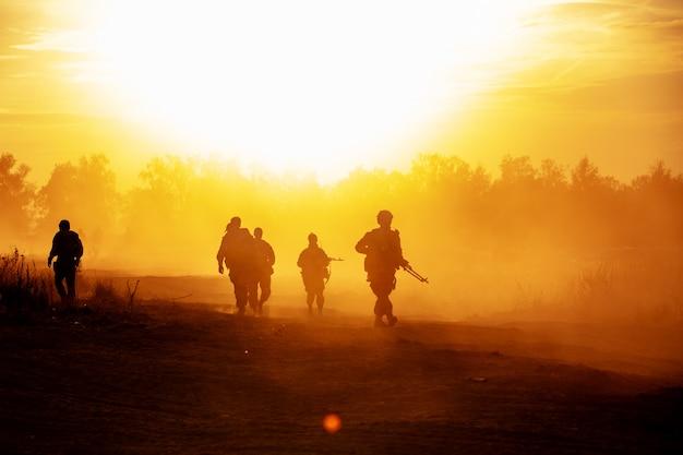 Los soldados de acción de silueta caminando sostienen armas es humo y puesta de sol y balance de blancos efecto de estilo de arte oscuro