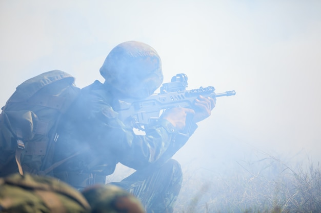 Soldados tailandeses que sostienen la pistola en su uniforme completo y realizan un entrenamiento completo en la montaña del bosque