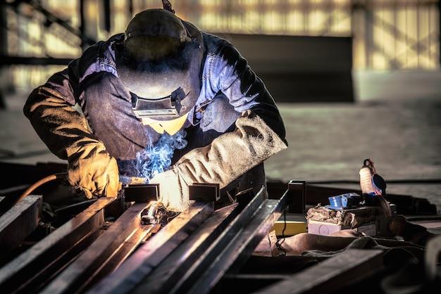 Soldadura de acero o soldador industrial en la fábrica