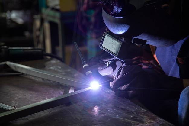 Soldadura de argón, trabajadores enmascarados y guantes de cuero para seguridad, soldadura de argón en la industria p
