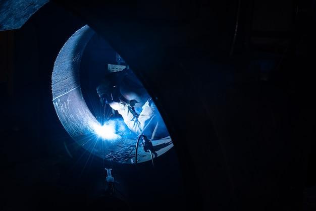 Soldadura de estructuras de acero y chispas brillantes con destellos de len en la industria del acero.