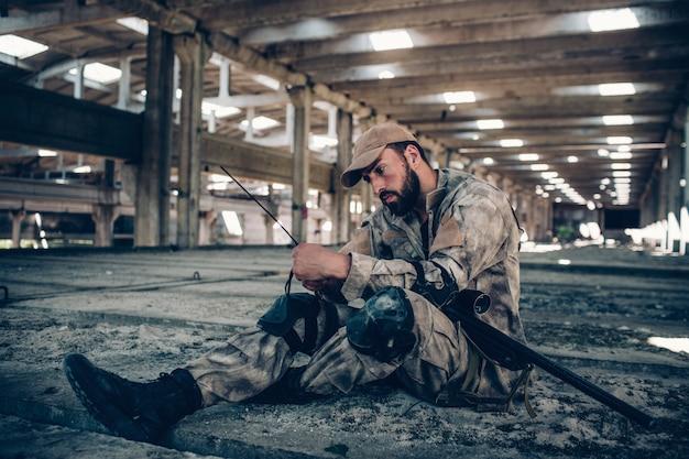 Soldier está sentado en el suelo y mira su radio portátil. lo está sosteniendo con ambas manos. guy curvó su mano izquierda y la extendió debajo de la derecha. él tiene el rifle acostado sobre su pierna izquierda.