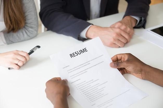 Solicitante afroamericano con currículum en entrevista de trabajo, vista de cerca