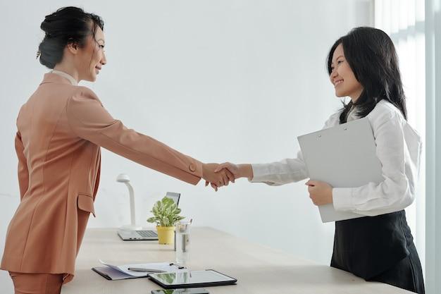 Solicitante de empleo joven sonriente y gerente de recursos humanos de la empresa un apretón de manos