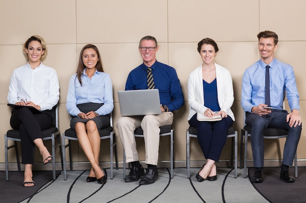 Los solicitantes cinco sonriente que se sienta en sala de espera