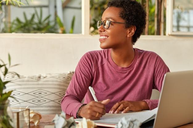 Solicitud de búsqueda en línea. sonriente niña o hipster juvenil mira positivamente a un lado