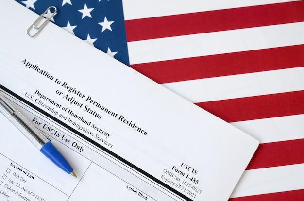 La solicitud i-485 para registrar la residencia permanente o ajustar el estado del formulario en blanco se encuentra en la bandera de los estados unidos con un bolígrafo azul del departamento de seguridad nacional