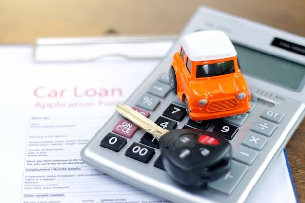Solicitud de préstamo de automóvil con llaves y modelo de automóvil