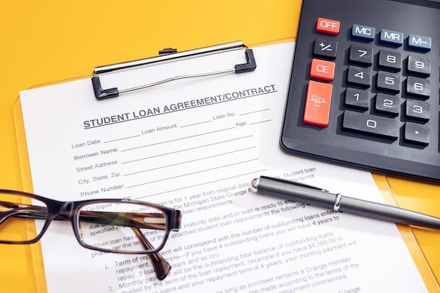 Solicitud de préstamo estudiantil en blanco con calculadora, bolígrafo y anteojos en la mesa sobre fondo amarillo