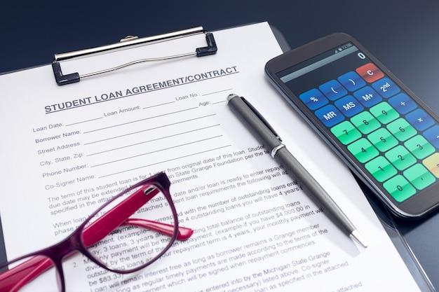 Solicitud de préstamo estudiantil en blanco con calculadora, bolígrafo y anteojos en la mesa